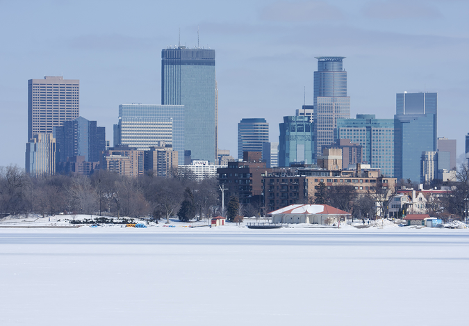 Minneapolis skyline across a frozen river – cold and long winters in the city